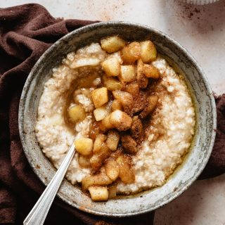 Apple oatmeal with cinnamon on top and a spoon inside the bowl