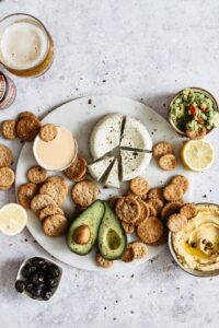 Healthy super bowl snacks: crackers served onto a marble platter with cheese and avocado