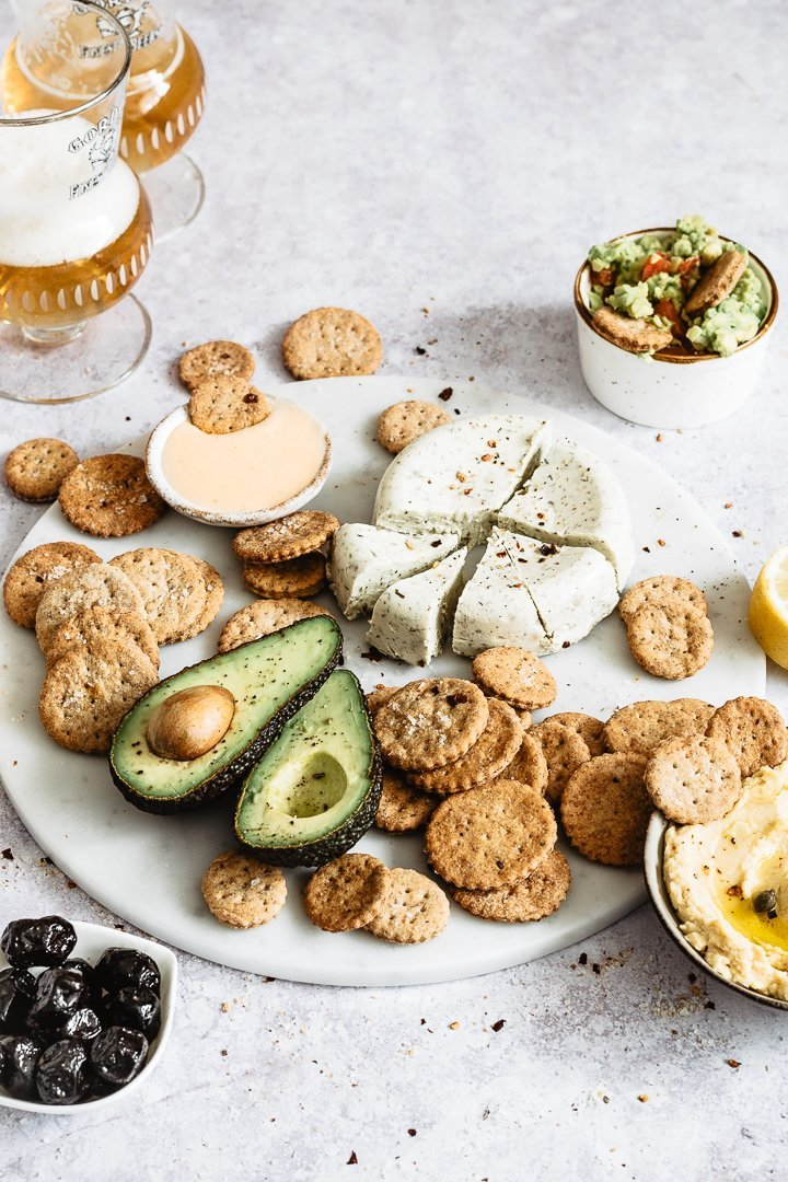 Healthy easy super bowl snack ideas: crackers served onto a marble platter with cheese, hummus and avocado