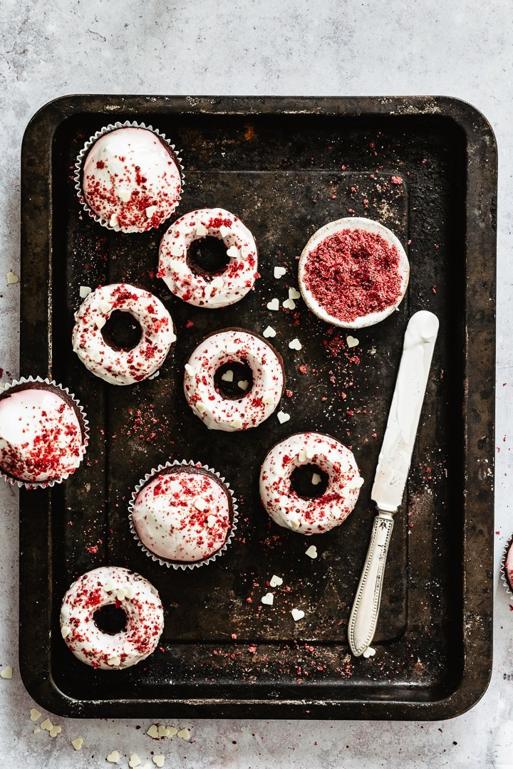 Red velvet donuts and cupcakes on a baking tray