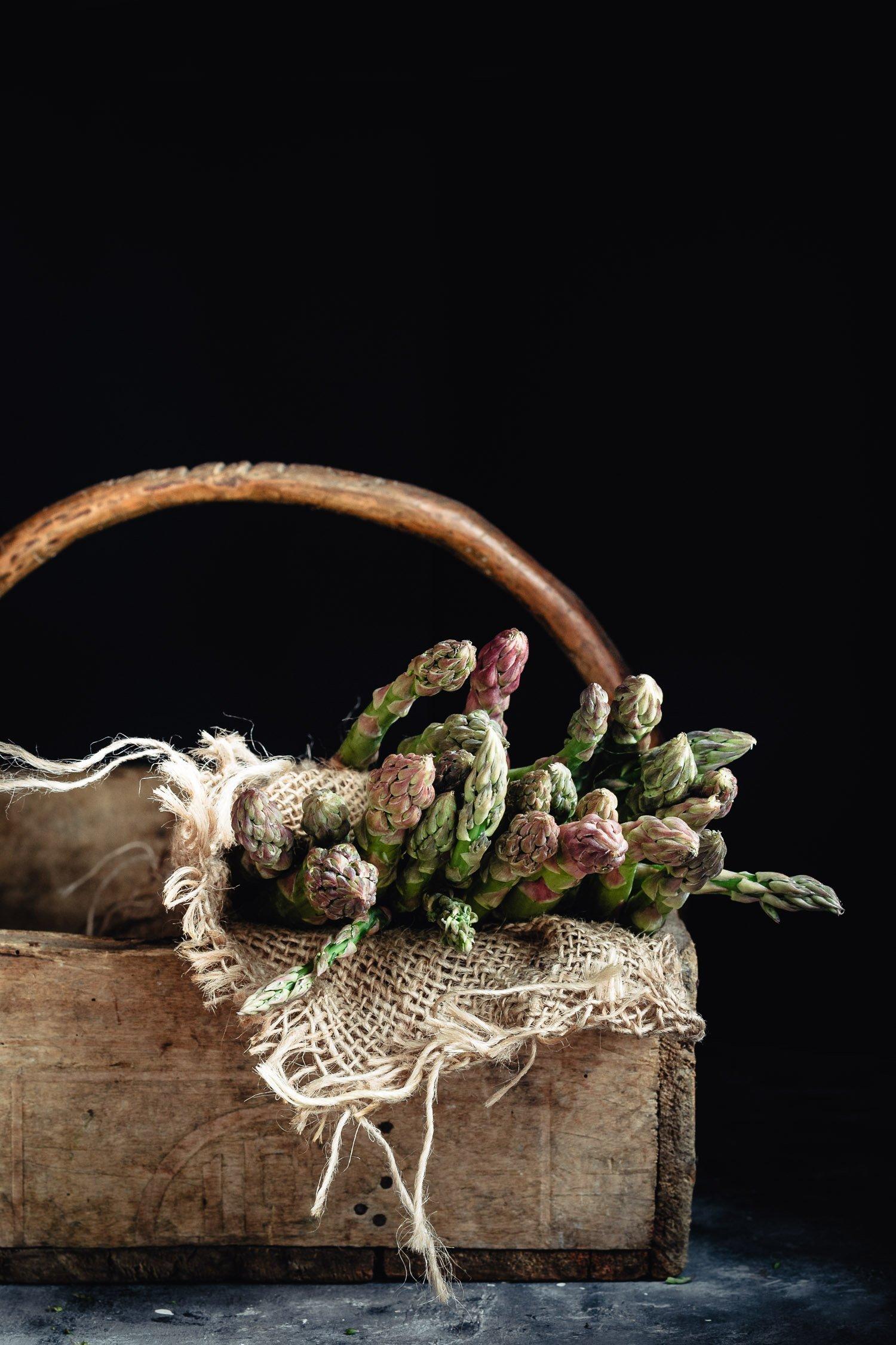 Raw asparagus into a basket
