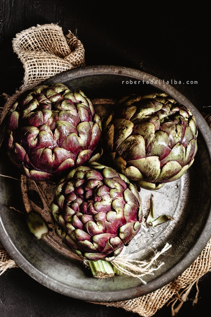 Raw globe artichokes onto a pan