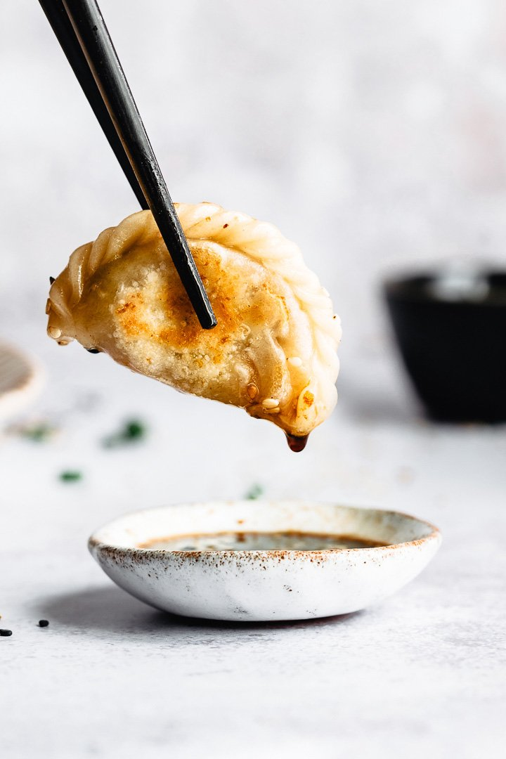 A single vegan potsticker dipped in its sauce.