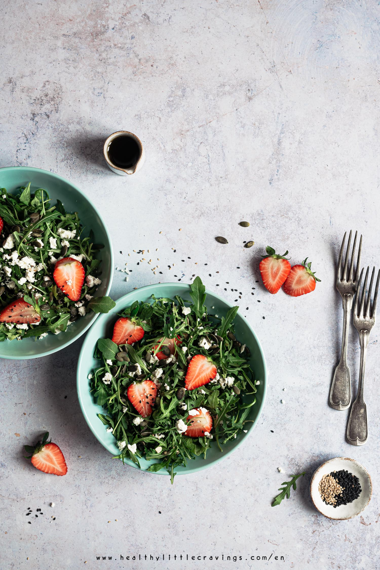 Strawberry arugula salad served into green plates