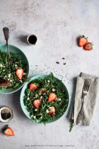Two plates with arugula salad and napkin on the side