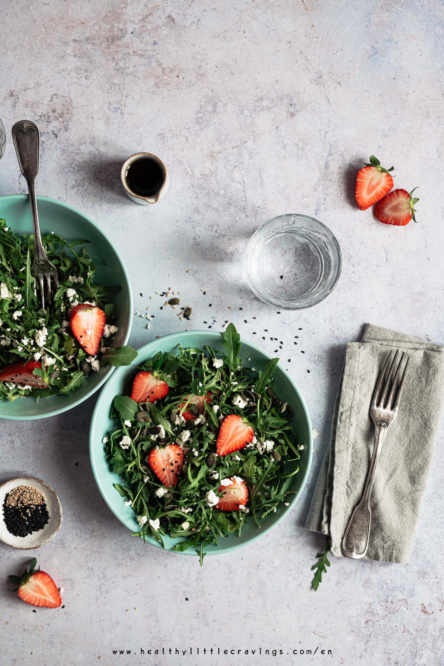 Two bowls of strawberry salad with arugula and feta