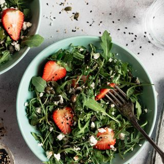Close up photo of a bowl of strawberry salad with feta and arugula