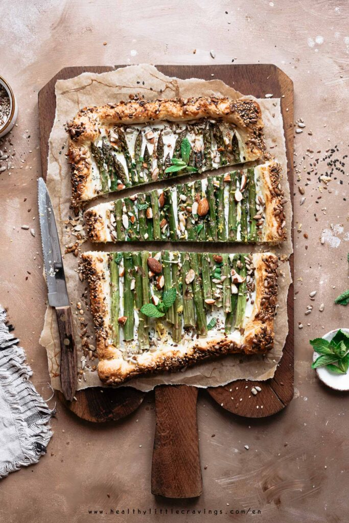 Slices of asparagus ricotta tart with almonds and mint