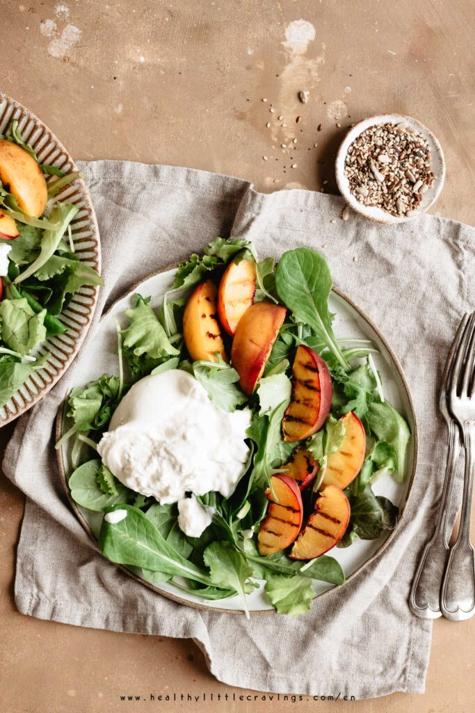 Grilled peach salad on a ceramic plate onto a napkin