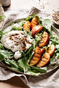 A grilled peach salad with burrata, seeds and vinaigrette