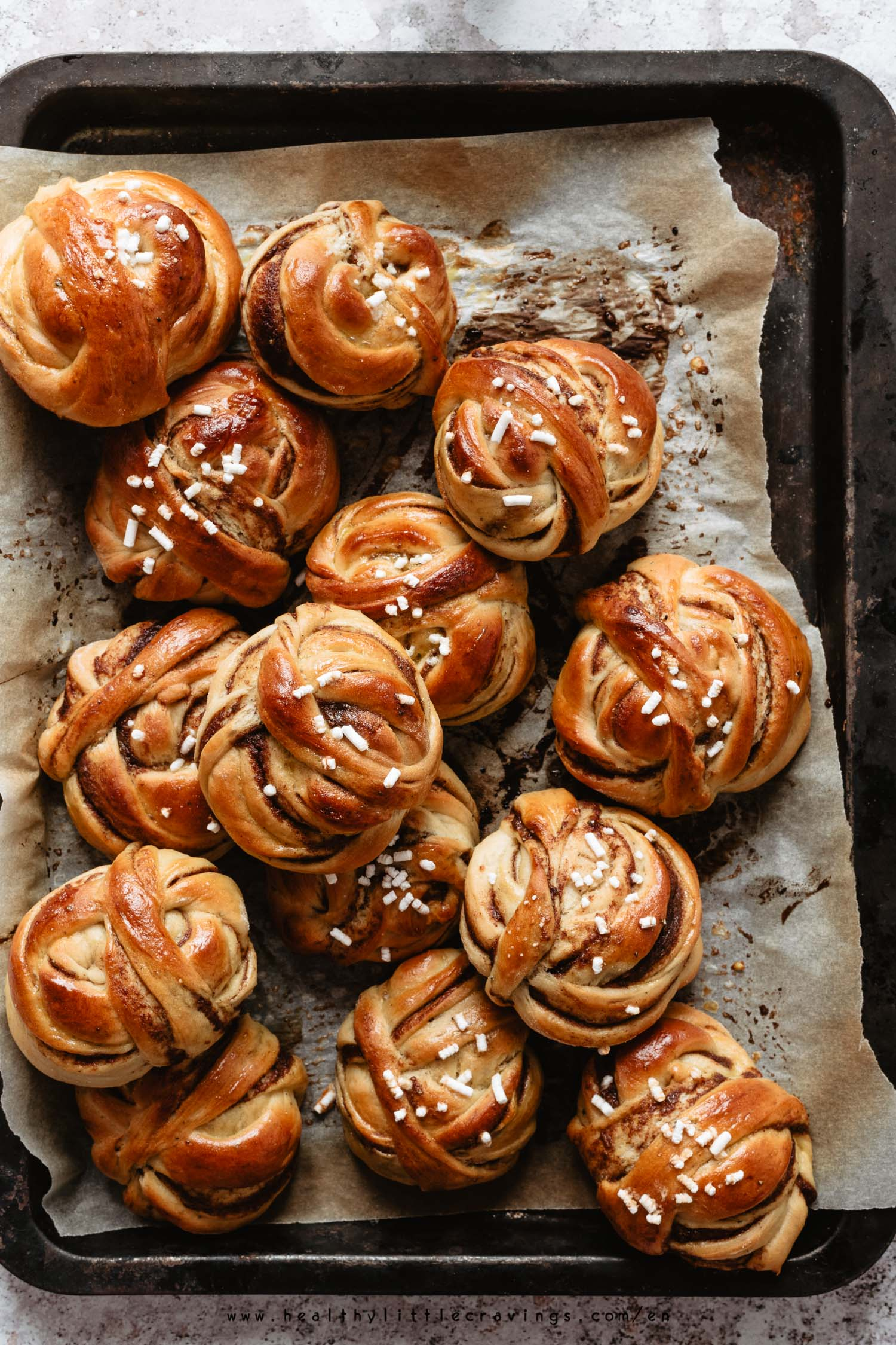 Swedish cardamom buns on parchment paper a baking tray