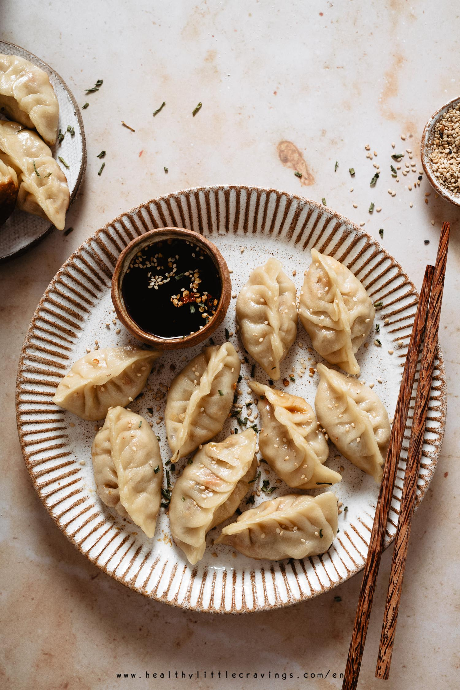 Chicken potstickers on a dish with a mini bowl of dipping sauce