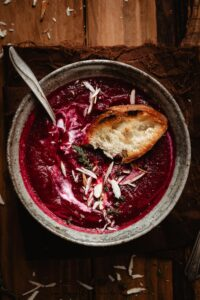 Baguette on a beet soup into a bowl