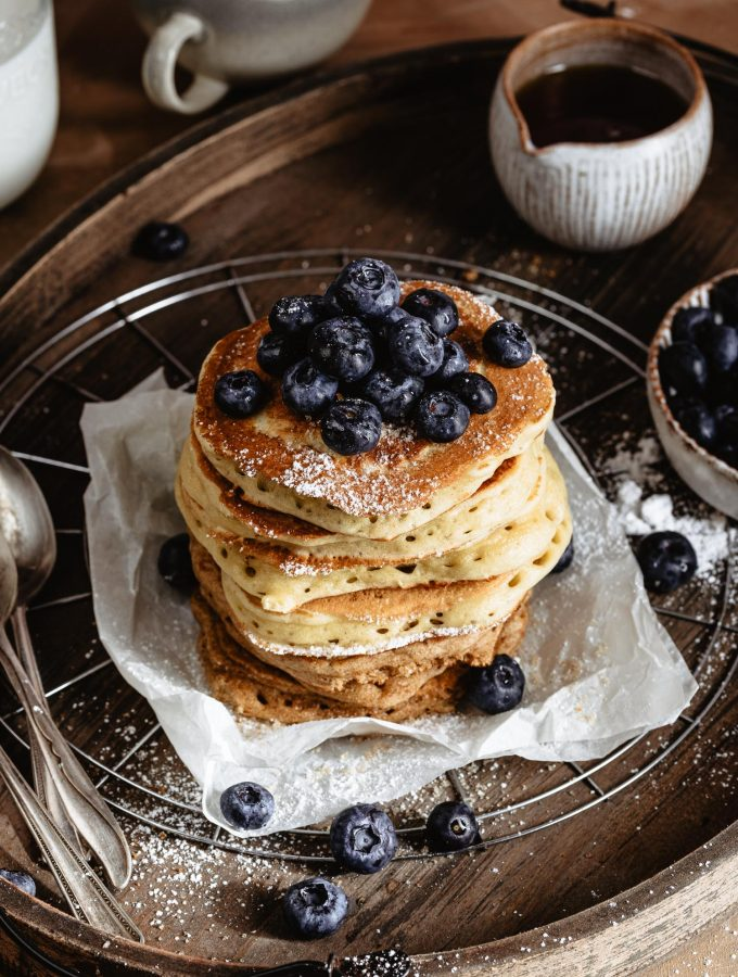 A delicious stack of fluffy pancakes on a piece of parchment paper