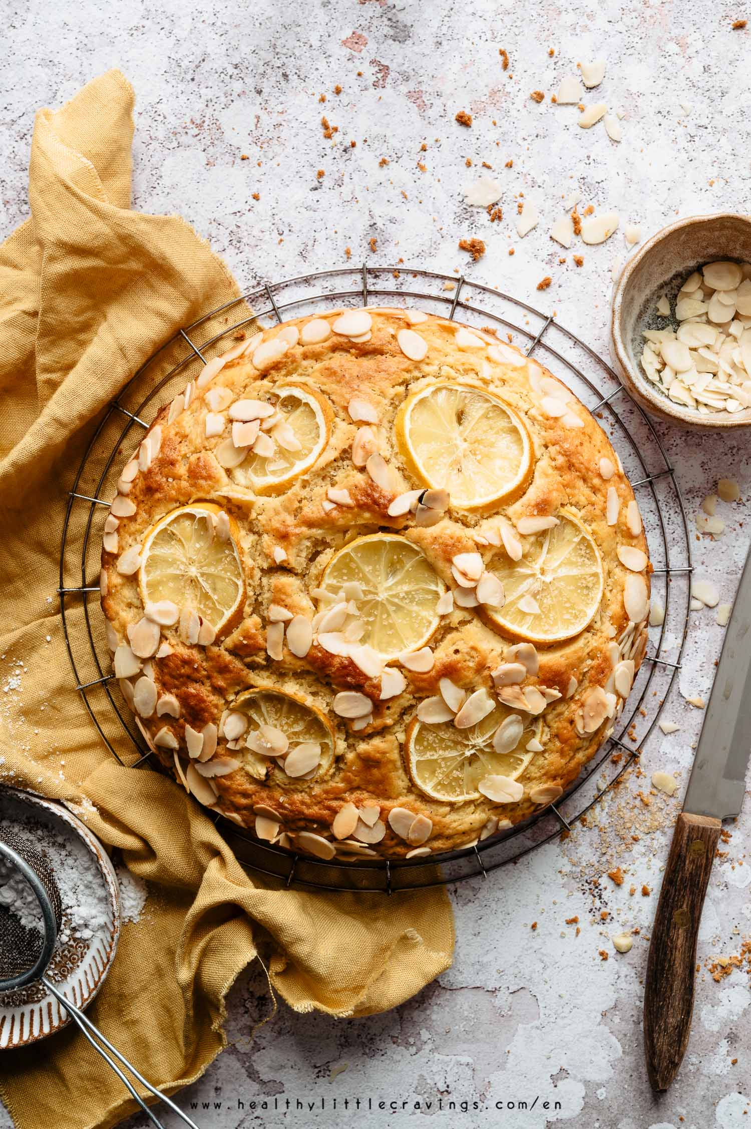 Lemon ricotta cake on a cooling rack with yellow napkin